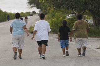 CAPTION : Members of health walk around Nauru airport.